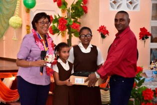 Students of the Joanna Primary school receive their laptops from Chairman, Yakusari Culture Centre, Mohabir Ramnauth as Minister of Public Telecommunications, Catherine Hughes looks on.